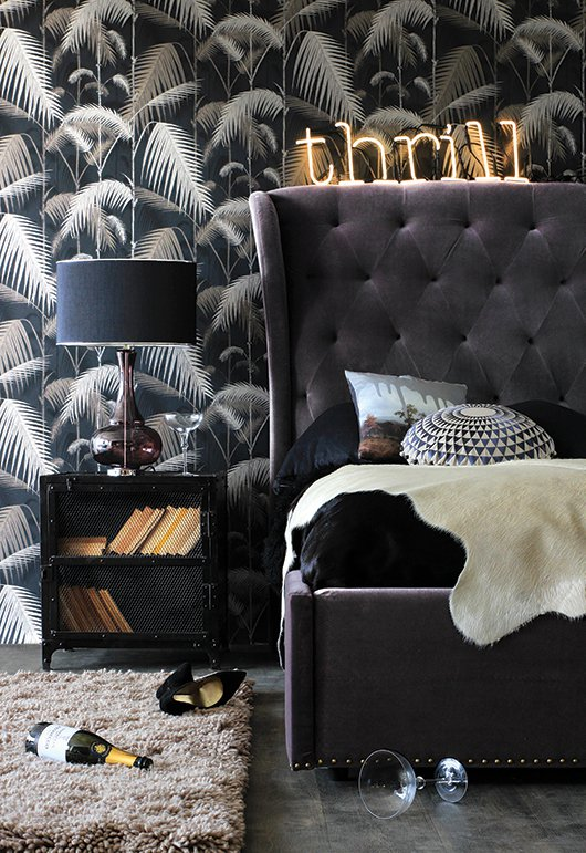 Grey-velvet-headboard-and-bed-with-stylish-decor-and-patterned-wallpaper